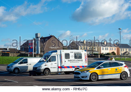 Mobile barber shop for male grooming in car park. Haircut shaving barber barbers bus. Deerpark Shopping Centre, Killarney, County Kerry, Ireland. - Stock Photo