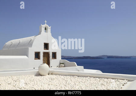 The iconic, whitewashed Church of Agios Vasilios, located in the town of Oia, island of Santorini, Greece, is shown on a summer afternoon day. - Stock Photo