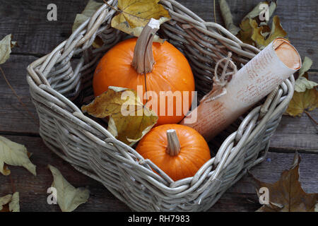 two pumpkins in a box on a wooden table - Stock Photo