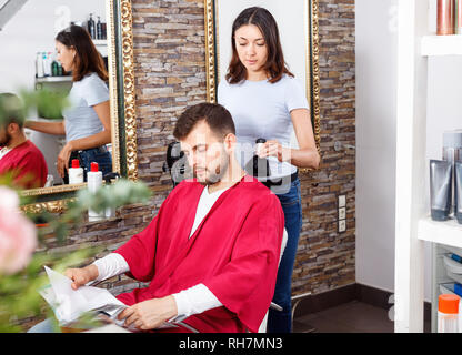 Cheerful pleasant positive smiling woman professional hairdresser cut male's hair in hairdressing salon - Stock Photo