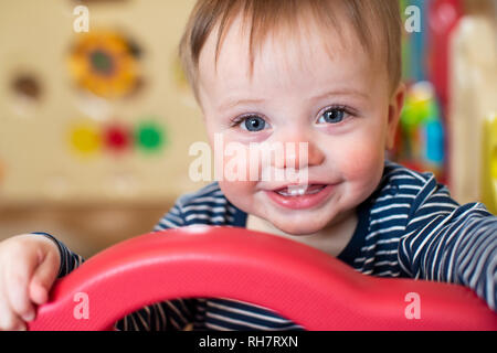 Portrait Of Cute Baby Boy Looking Out Of Play Pen And Smiling At Camera - Stock Photo