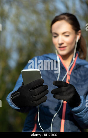 Young Woman Choosing Music To Listen To On Mobile Phone Before Exercising In Park - Stock Photo