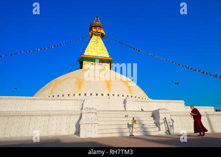 A Tibetan Buddhist monk circumambulating the big stupa of Bodhnath (Baudha), Kathmandu, Nepal, a pigeon flying over his head - Stock Photo