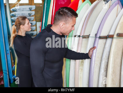 Young man and woman dressed surfing suits checking surfboards on racks in surf club. Focus on man - Stock Photo
