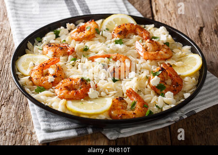 Main course orzo pasta with shrimps, feta cheese, herbs and lemon close-up on a plate on the table. horizontal - Stock Photo