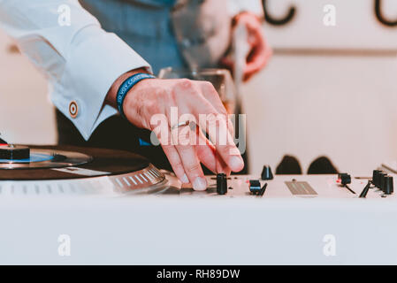 Crop hand of male in shirt using DJ equipment near glass of beverage on blurred background - Stock Photo