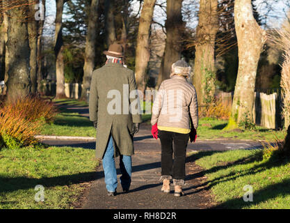 Middle aged or senior couple dressed in warm Winter clothing with scarf and hat walking together on a country path in Winter in the UK. - Stock Photo
