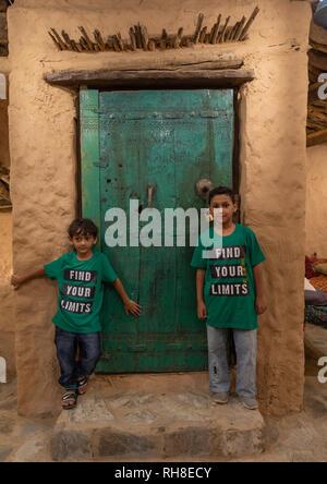 Saudi boys standing in front of al Baitul Jabali house, Jizan Province, Jizan, Saudi Arabia - Stock Photo