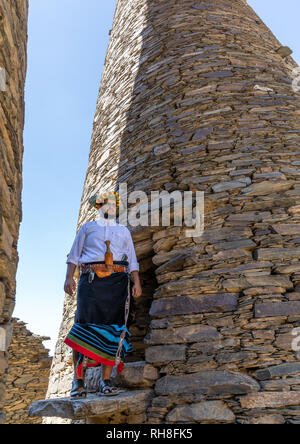 Portrait of a flower man wearing a floral crown on the head near a stone watchtower, Jizan Province, Addayer, Saudi Arabia - Stock Photo