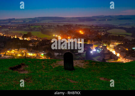 Nightime photograph overlooking Corfe village from nearby hilltop with waymarker stone. Corfe village, Dorset, England - Stock Photo