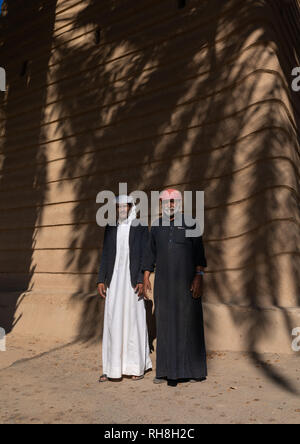 Saudi farmers standing in front of a traditional old mud house, Najran Province, Najran, Saudi Arabia - Stock Photo
