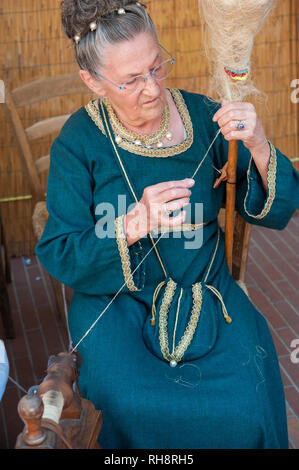 Old woman in medieval clothes demonstrating traditional wool spinning. - Stock Photo