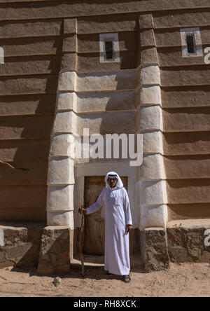 Saudi man standing in front of a traditional old mud house, Najran Province, Najran, Saudi Arabia - Stock Photo