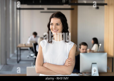 Smiling confident motivated female leader looking away dreaming of future - Stock Photo