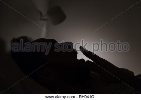 Silhouette of adult sleepy yawning man covering mouth with hand awake late at night in bed, can not fall asleep/ lying in bed, sleepy tired. - Stock Photo