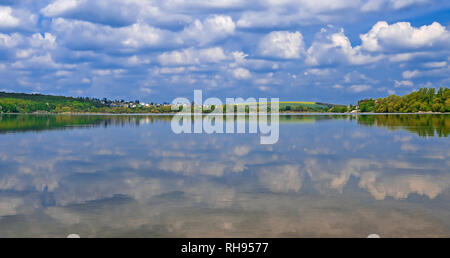 A bridge leads to an island in the middle of a lake on which tall green trees grow against a blue sky with clouds - Stock Photo