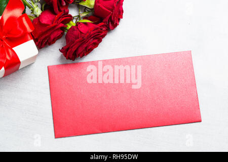 Holiday background or greeting card. Red roses, envelope and present box on white stone table. Space for your text. - Stock Photo