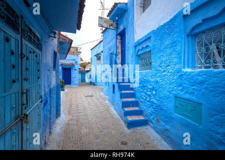 Beautiful view of the blue city in the medina. Traditional moroccan architectural details and painted houses in CHEFCHAOUEN, MOROCCO. street with door - Stock Photo