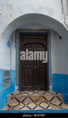 Typical, old, brown intricately carved, studded, Moroccan riad door and door-frame and old house. blue city in the medina of CHEFCHAOUEN, MOROCCO - Stock Photo