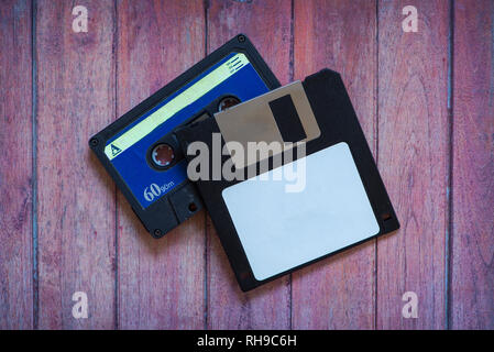 Antique pc diskettes and cassettes on a brown wooden background - Stock Photo