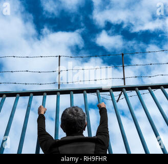 Rear view of man looking through steel barred  fence topped with barbed fence. Brexit, immigration, asylum... concept - Stock Photo