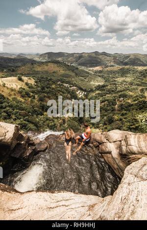 Natural pool on top of waterfall at Diyaluma Falls, Sri Lanka. Couple in pool. - Stock Photo