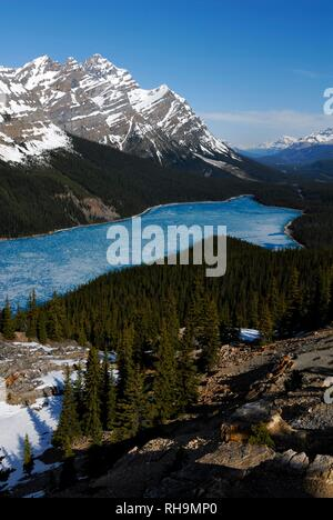 Glacial Peyto Lake in spring with a thin sheet of ice, the summit of Mt. Patterson at the back, Banff National Park - Stock Photo