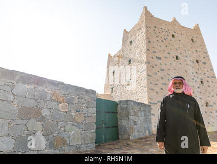Saudi man standing in front of an old traditional stone house, Asir province, Al-Namas, Saudi Arabia - Stock Photo