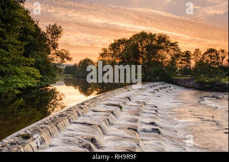 Scenic colourful sunset sky over rural landscape (water gently flowing down weir steps) - River Wharfe, Burley in Wharfedale, Yorkshire, England, UK. - Stock Photo