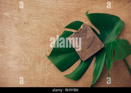 Natural soap on wooden background with green monstera leaf. Plastic free beauty essentials. Zero waste concept, flat lay with copy space. Sustainable  - Stock Photo