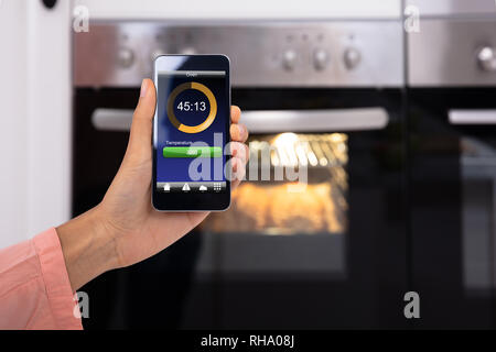 Close-up Of Woman's Hand Operating An Oven Application With Mobile Phone App - Stock Photo