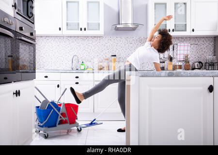 Close-up Of A Young African Woman Slipping While Mopping Floor In The Kitchen - Stock Photo