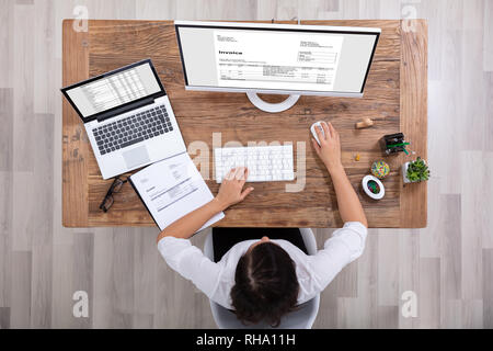 Young Businesswoman Looking At Invoice On Computer Screen In The Office - Stock Photo