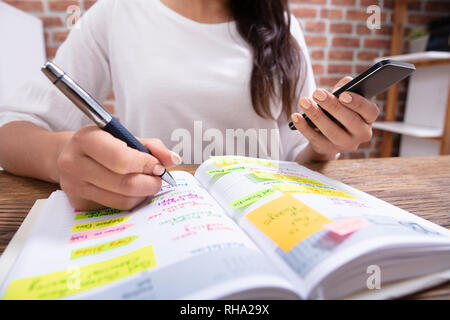 Close-up Of A Businesswoman Holding Cellphone Writing Schedule In The Diary With Pen - Stock Photo