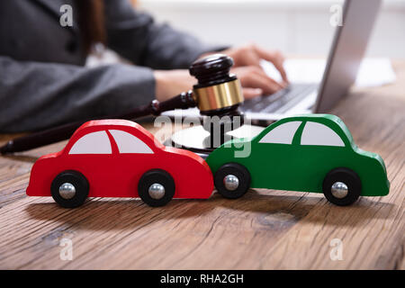 Small Green And Red Car In Front Of Gavel And Mallet And Businessperson Using Laptop - Stock Photo