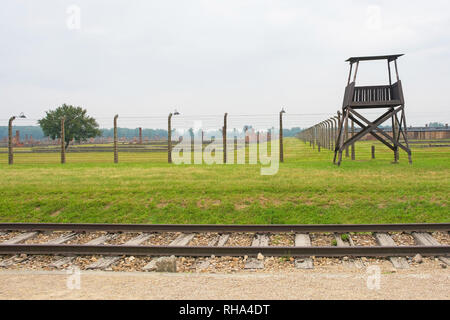 A guard tower and barbed wire fences in the Birkenau Auschwitz II concentration camp in Poland - Stock Photo