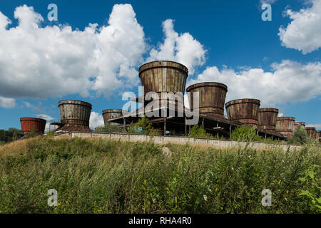 Old rusty cooling towers against a blue sky - Stock Photo