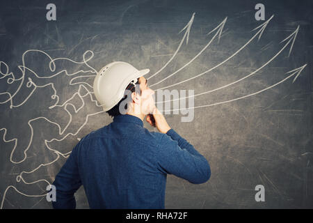 Rear view concentrated man engineer wearing protective helmet thoughtful looking at blackboard as mesh lines come through head and transform into stra - Stock Photo