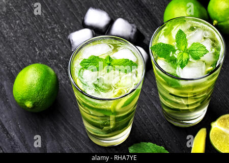 Summer mojito cocktail with mint and ice in glass on black wooden table(selective focus). - Stock Photo