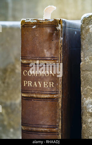 Closeup of an old leather-bound prayer book on a stone shelf in an ancient church - Stock Photo