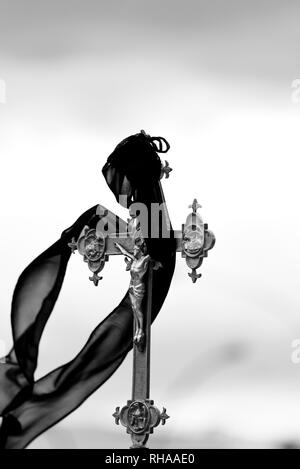 Crucifix with drape moved by the wind - religious procession - Stock Photo