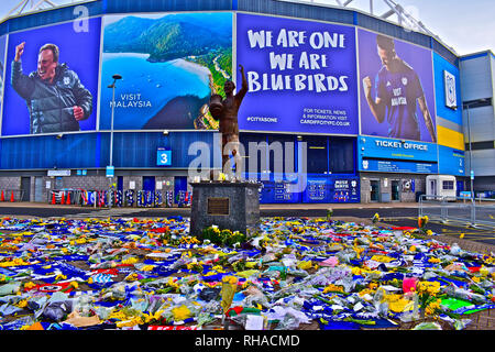 Recent tragic loss of new signing Emiliano Sala in plane crash from Nantes. Fan's salute player with floral tributes outside Cardiff City's Stadium. - Stock Photo