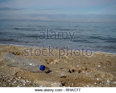 Transparent plastic water bottle abandoned on the sand - Stock Photo
