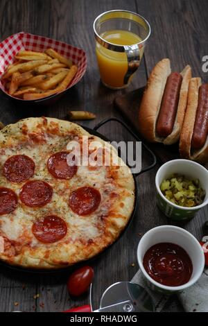 Party game day food Homemade Pizza hot dogs fries juice and dips - Super bowl food concept overhead view - Stock Photo
