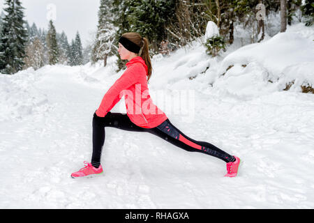 Young sport woman doing exercises during winter training outside in winter mountains wearing warm clothing gloves in snow weather - Stock Photo