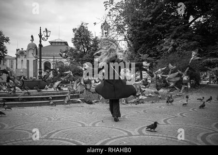 Black and white photo of beautiful girl holding DSLR camera who is playing and chasing flock of pigeons in Sofia in cloudy winter day a public city sq - Stock Photo