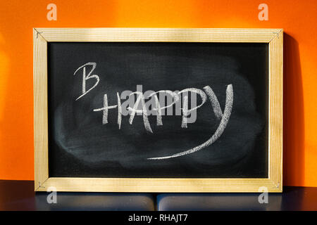 Black board with text B Happy written on chalk - Stock Photo