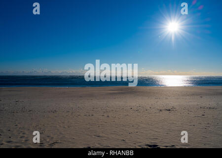Photo of Point Pleasant beach on a bitterly cold winter morning lit up by a brightly shining sun. - Stock Photo