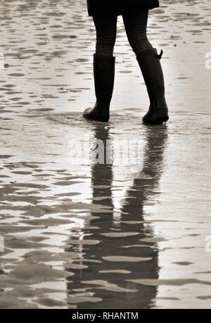 loan female figure wearing wellington  boots walking over wet sandy beach at low tide - Stock Photo