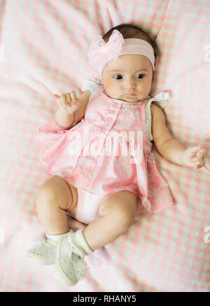 A little baby in a pink dress lies on a blanket and poses - Stock Photo